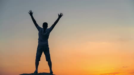 Success achievement running or hiking accomplishment business and motivation concept with man sunset silhouette celebrating arms up raised outstretched trekking climbing running outdoors in nature. RAW video record. Stock Footage