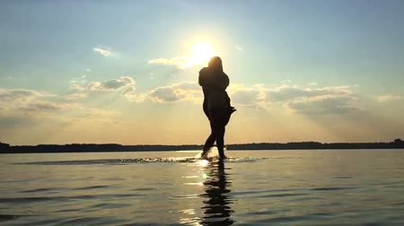 SLOW MOTION: Love Sunset. Two lovers on a background sunset swirling water