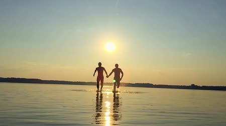 Two happy homosexual running on water at sunset. Slow Motion video