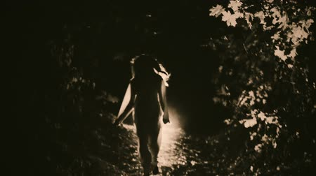 A girl in a white dress running night forest. The dramatic scene of horror.