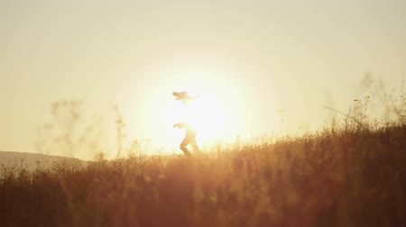 Boy with the airplane in the hands of running on a hill at sunset. Slow motion