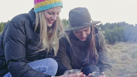 Happy but cold lesbian girls are sitting on the ground with cups of tea and kissing Stock Footage