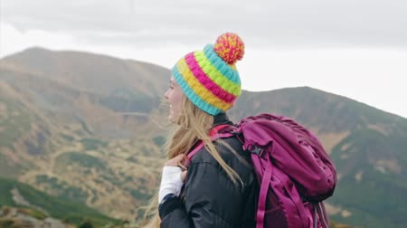 Young backpacker standing on top of a mountain Stock Footage