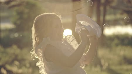 Little girl chasing soap bubbles outdoors