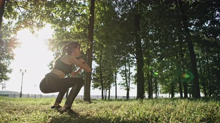 Active woman doing squats while exercising in park on sunny day. Stock Footage