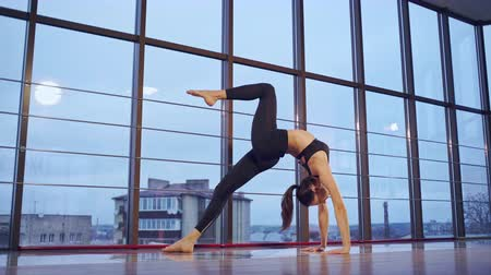 braços levantados : Young woman doing yoga upward bow pose