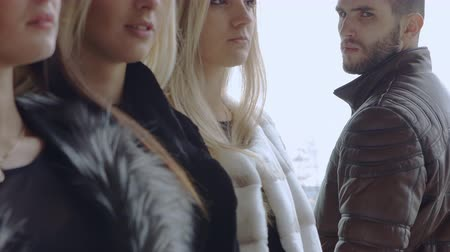 triangolo amoroso : A young bearded man looks at three women in expensive furs and turns away from them. Family concept mistresses and macho. Filmati Stock