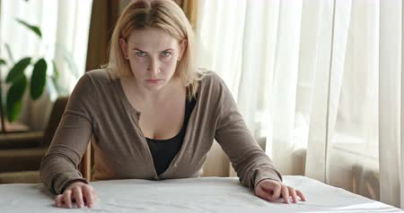 bağırma : Nervous adult woman has a strong, angry look at the camera while sitting at the table in the room near the window