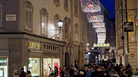 estuque : Salzburg, Austria - December 27, 2017:Beautiful night narrow alley with brightly lit shop windows in old stone buildings and festive garlands at night in Salzburg, Austria