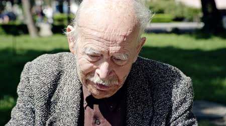 büyükbaba : Hot tired old man with a cane in a park wiping the sweat off his forehead with a handkerchief then taking off his cap