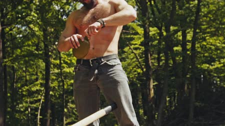 hidratar : Strong shirtless man splitting logs in woodland