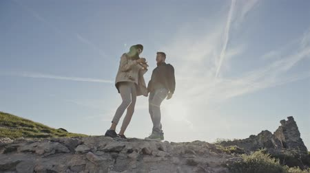 épico : A couple of happy tourists jumping from joy to the top of the mountain against the background of the sunrise and clear blue sky Stock Footage