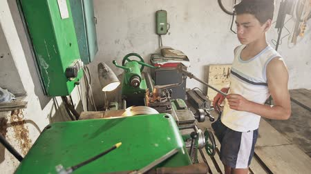 lado : Male teenager in casual outfit taking metal tool from lathe while standing in professional workshop Stock Footage