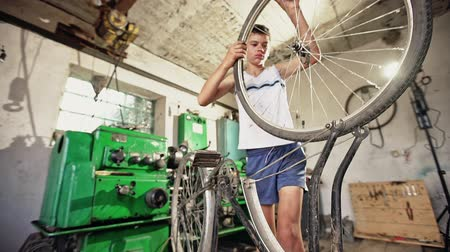 ajustando : Teenager putting wheel on bicycle