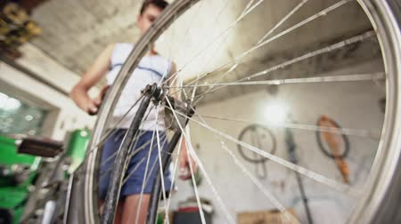 ajustando : Teenager screwing wheel to bicycle