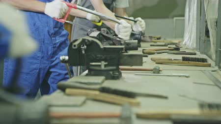 dungarees : Row of workers working with hand saws over a workbench littered with tools in a factory production line in a close up low angle view