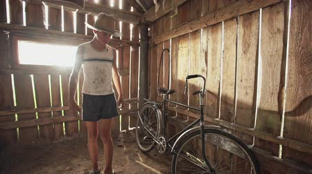 дверной проем : Adolescent country boy in straw hat taking off the cover from vintage bicycle and rolling it out of wooden hangar - slow motion