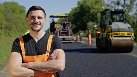 üresedés : Portrait of a happy worker who repairs roads on the background of asphalt roller and other equipment. Happy employee looks at the camera.