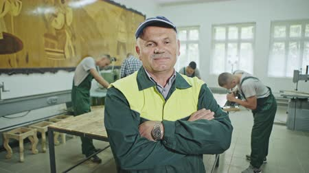 workman : Mature man in cap and overall standing with hands crossed in joinery shop with working young men on background.