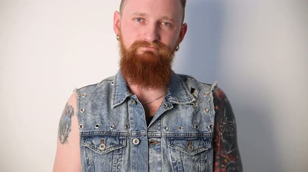 modern manhood : modern youth. calm portrait of a good biker with tattoos and a stylish beard and mustache in a denim waistcoat. Stock Footage