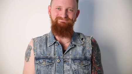 modern manhood : modern youth. a cheerful portrait of a kindly smiling biker with tattoos and a stylish beard and mustache in a denim vest. Stock Footage