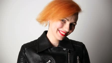 rty : modern youth. calm portrait of a smiling woman of unusual appearance with red hair and creative hairstyle in a leather jacket.