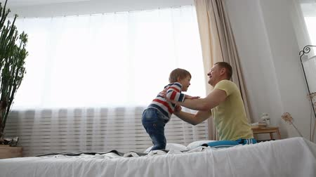 общаться : happy modern family. Dad with a small son is having fun on the bed in the bedroom.
