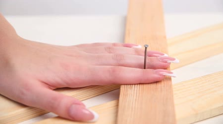 provokativní : a sexy woman hammers a nail with a hammer in a wooden construction. hands with beautiful manicure close-up.