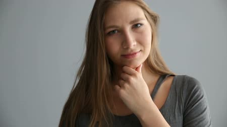 okey : portrait of a blond girl of European appearance in casual clothes on a gray background Stock Footage