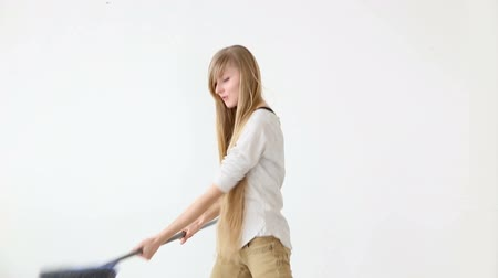 певец : Cheerful attractive teen girl sings and dances with a broom like a microphone over white background. Стоковые видеозаписи