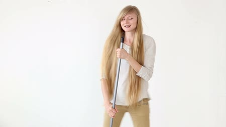vassoura : Cheerful attractive teen girl sings and dances with a broom like a microphone over white background. Vídeos