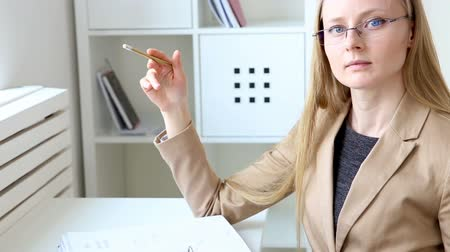 brasão : young beautiful woman in business style with glasses and documents works in an office in the workplace