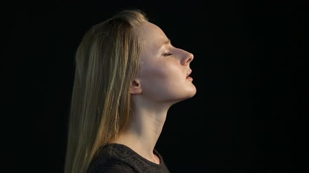 homály : emotional portrait of a blond girl on a black background