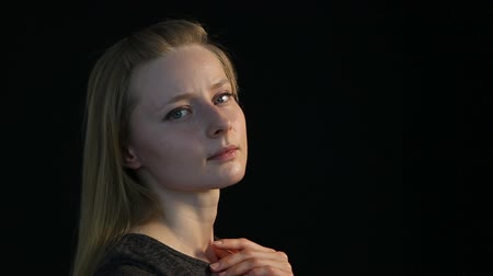 cheerless : emotional portrait of a blond girl on a black background