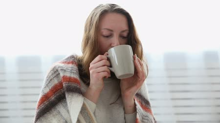 přehoz : a simple woman drinks tea wrapped in a warm woolen blanket