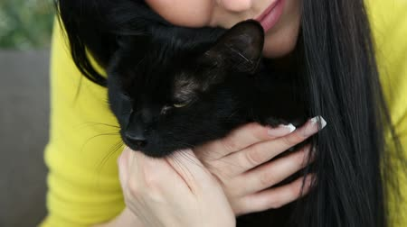 kürk : love for pets. beautiful dark-haired girl with a black cat is relaxing at home in the living room on the couch. Stok Video