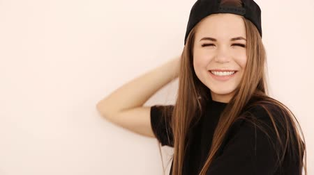 рэп : teenage girl in trendy hip hop clothes and cap posing against white wall Стоковые видеозаписи