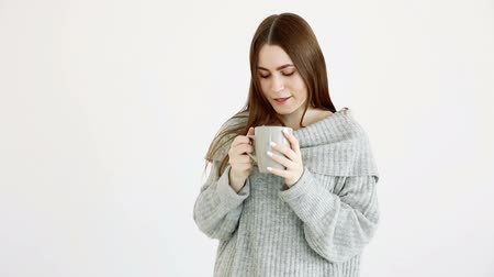 меланхолия : beautiful girl of European appearance in a warm sweater drinks hot tea by the white wall.