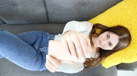 mobile music : beautiful girl doing selfie on mobile phone on sofa at home