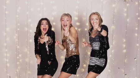 choque : 3 beautiful girls at a party blowing up a cracker with confetti - slow motion Vídeos
