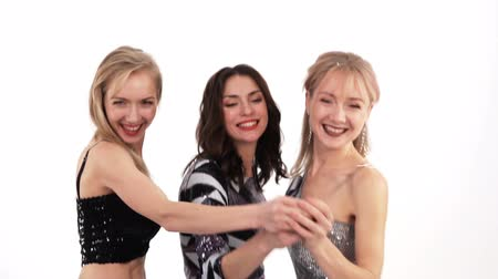 bengália : 3 beautiful cheerful girls with bengal lights dancing in the studio on a white background - slow motion Stock mozgókép