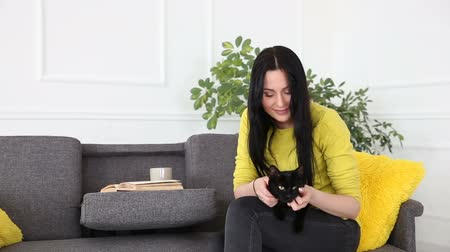 ronronar : love for pets. beautiful dark-haired girl with a black cat is relaxing at home in the living room on the couch. Stock Footage