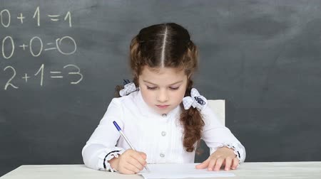 elsődleges : little girl is sitting at his desk at school Stock mozgókép