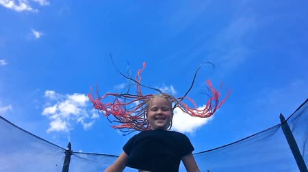 гимнастика : carefree childhood, happy summer. beautiful girl with African pigtails jumping on a trampoline - slow motion