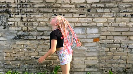 pigtail : stylish girl waving African pigtails near a brick wall - slow motion