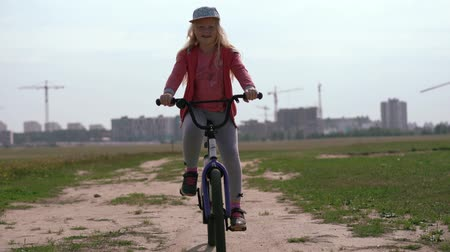 ciclista : healthy lifestyle - girl riding a bicycle across the field near the city Stock Footage