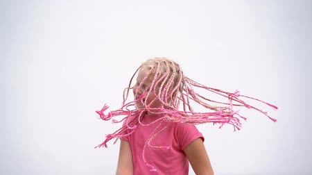 braids : the beauty of slow motion - portrait of a beautiful light-skinned little girl of a non-standard modern appearance - with pink African plaits of zizi
