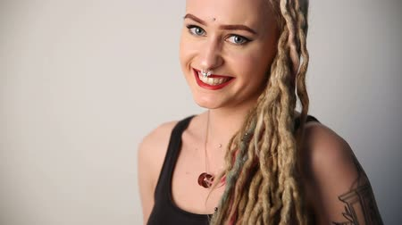 korhadt : modern youth. portrait of a cheerful beautiful girl of unusual appearance - dreads, piercings and tattoos. Stock mozgókép