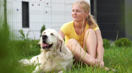 love for pets - a young blonde woman resting with her dog on the grass