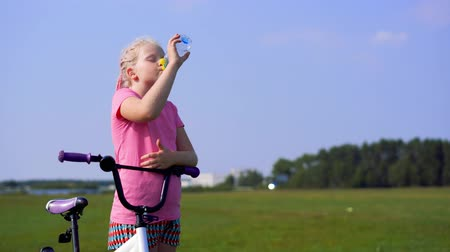healthy lifestyle - girl drinks water in a field with a bicycle